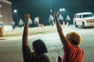 Ferguson Protesters sitting with fists in the air. Police line in the distance.