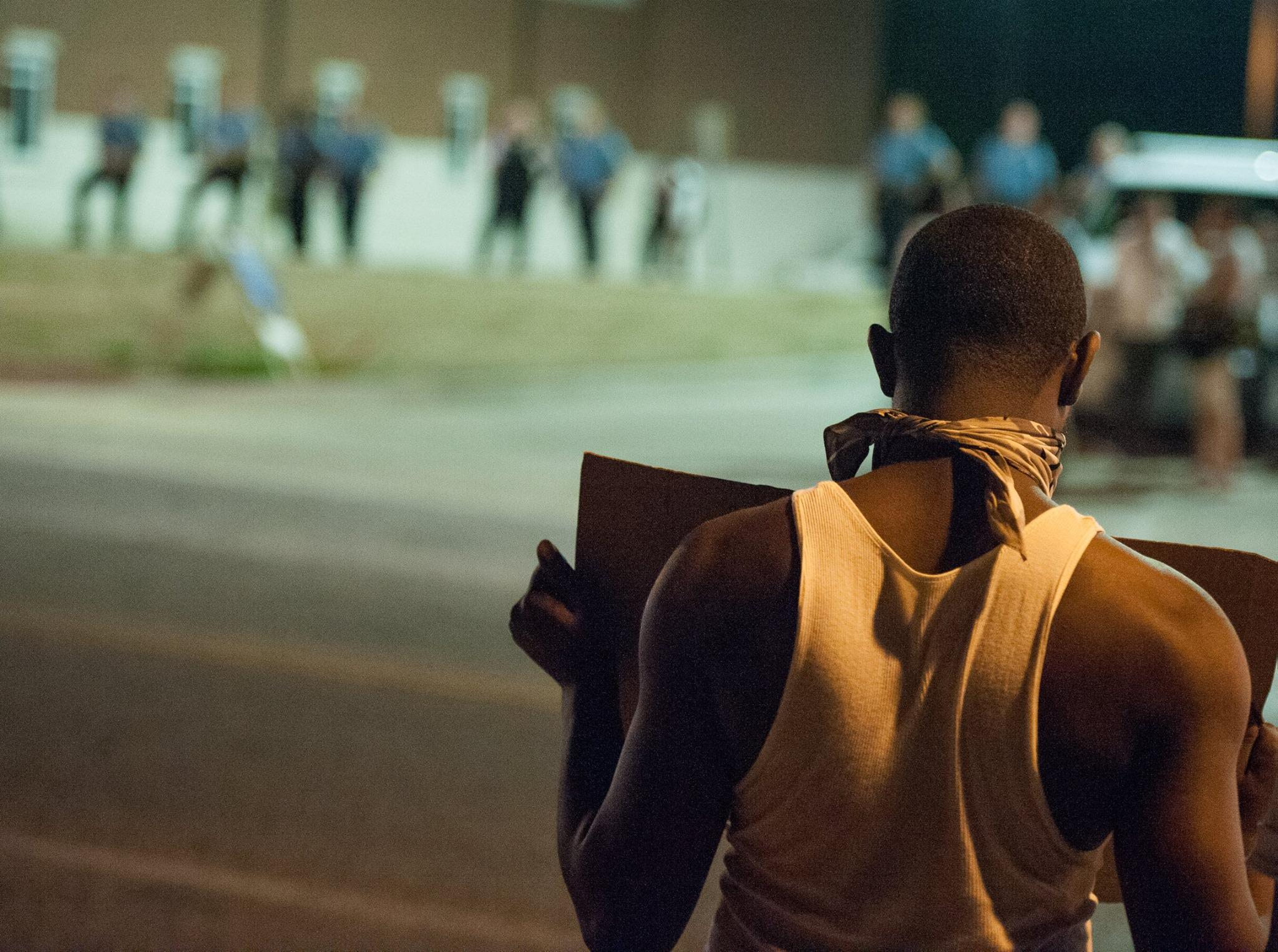 Ferguson Protester holding a sign, police in background.